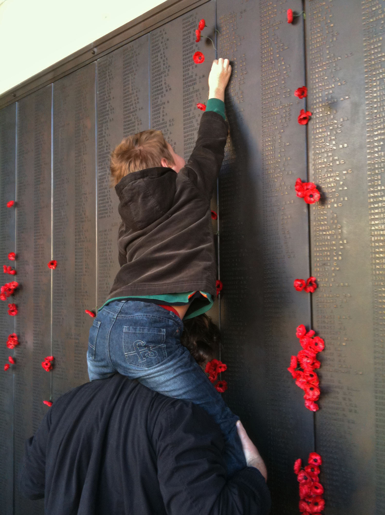 Placing a poppy in the Roll of Honour